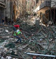 Människor arbetar med att ta bort bråte från gatorna från explosionerna.  Bilal Hussein / TT NYHETSBYRÅN