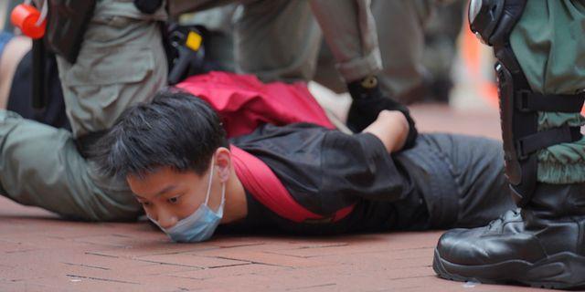 En demonstrant grips under dagens protester. Vincent Yu / TT NYHETSBYRÅN