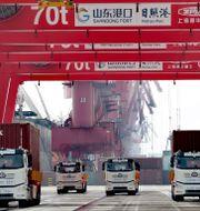 Lastbilar i kinesisk hamn. TT NYHETSBYRÅN