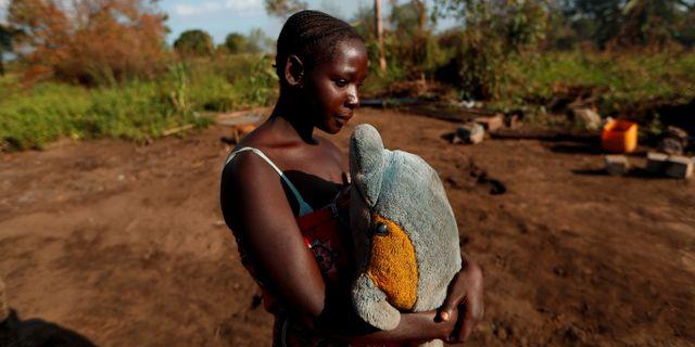 Maria Jofresse, 25, håller om ett gosedjur hon fick som barn. Hon står på platsen där hennes hus stod innan cyklonen Idai drog fram. Zohra Bensemra / TT NYHETSBYRÅN
