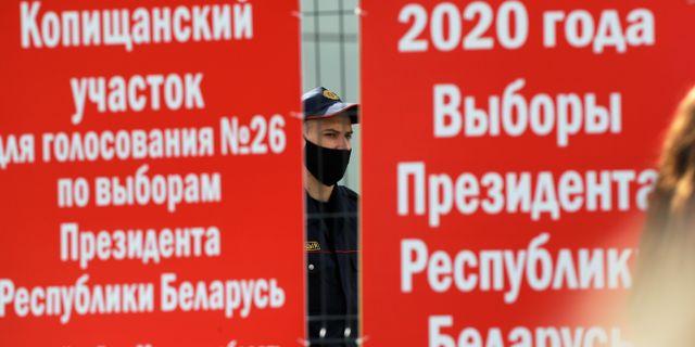 En polis syns bakom ett staket intill en vallokal i Minsk.  Sergei Grits / TT NYHETSBYRÅN