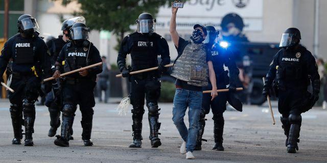 En demonstrant går intill poliser i Louisville igår. Darron Cummings / TT NYHETSBYRÅN