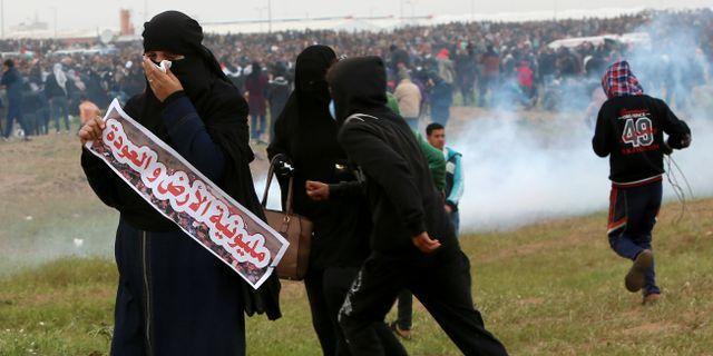 Demonstranter tar skydd från tårgas nära stängslet vid gränsen mot Israel.  Adel Hana / TT NYHETSBYRÅN