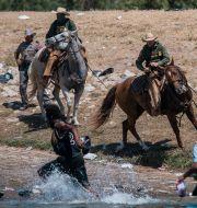 Gränsvakter och migranter vid Del Rio. Felix Marquez / TT NYHETSBYRÅN