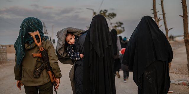 Kvinnor som uppges vara medlemmar i IS bevakas av en kvinnlig SDF-soldat. BULENT KILIC / AFP