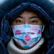 A woman wearing a face mask to help curb the spread of the coronavirus walks on a street during the morning rush hour in Beijing, Wednesday, Dec. 16, 2020 Andy Wong / TT NYHETSBYRÅN