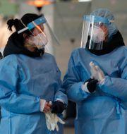 Sjukhuspersonal i skyddsutrustning vid en testanläggning i Seoul.  Lee Jin-man / TT NYHETSBYRÅN
