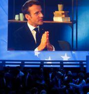 Macrons intervju visas på en storbildskärm under ett möte där hans parti En Marche har samlats. CHARLES PLATIAU / TT NYHETSBYRÅN