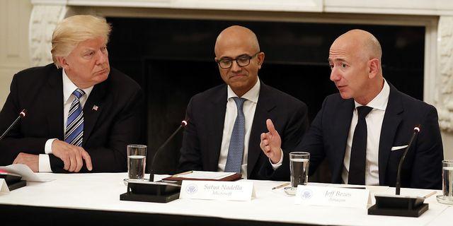 Donald Trump och Jeff Bezos (höger) på middag i Vita huset förra sommaren. I mitten: Microsofts koncernchef Satya Nadella. TT