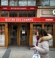 Arkivbild: En kvinna passerar en stängd restaurang vid Champs-Elyseeavenyn under den första coronanedstängningen i våras.  LIONEL BONAVENTURE / TT NYHETSBYRÅN