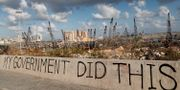 """""""Min regering gjorde det här"""". Slagord skrivna vid explosionsplatsen. Hussein Malla / TT NYHETSBYRÅN"""