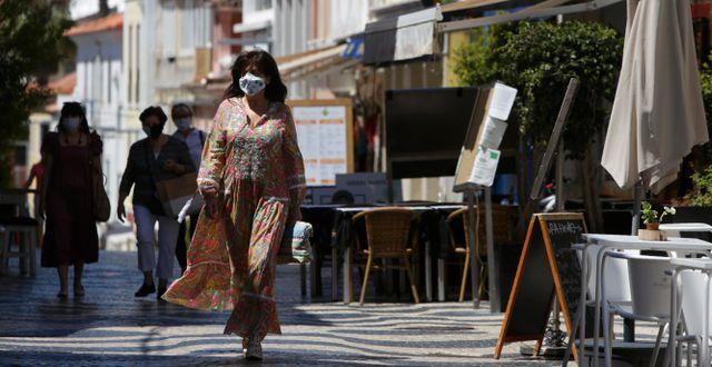 Kvinna går förbi tom restaurang i Cascais utanför Lissabon.  Armando Franca / TT NYHETSBYRÅN