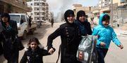 Kvinnor springer för att undkomma en explosion i Afrin på söndagen. NAZEER AL-KHATIB / AFP