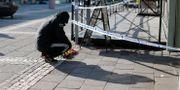 En man lägger blommor vid polisens avspärrningar på Vårväderstorget i Göteborg. Adam Ihse/TT / TT NYHETSBYRÅN