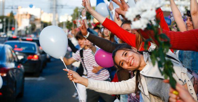 Människor i Minsk viftade med ballonger och blommor när de samlades för att protestera mot presidentvalet Sergei Grits / TT NYHETSBYRÅN