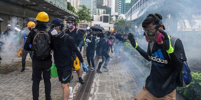 Demonstranter reagerar på tårgasen. NICOLAS ASFOURI / AFP