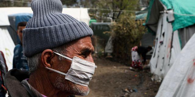 Man med munskydd i Morialägret på Lesbos. Elias Marcou / TT NYHETSBYRÅN