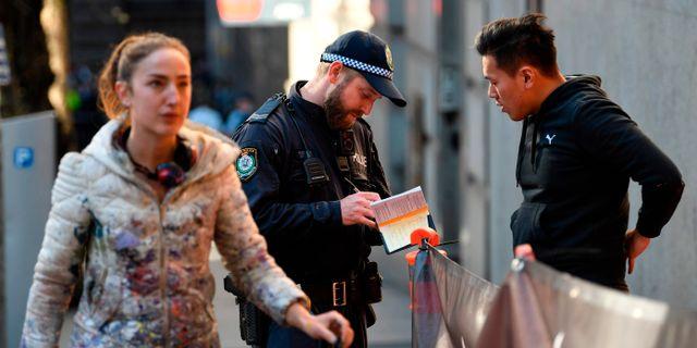 Polis talar med ett vittne till knivdådet i Sydney. SAEED KHAN / AFP