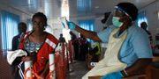 Vårdpersonalen undersöker en kvinnas kroppstemperatur vid gränsen mellan Uganda och Kongo-Kinshasa.  STRINGER / TT NYHETSBYRÅN