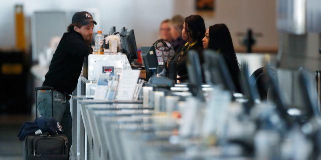 Illustrationsbild: En passagerare står vid United Airlines disk  på flygplatsen i Denver.  David Zalubowski / TT NYHETSBYRÅN