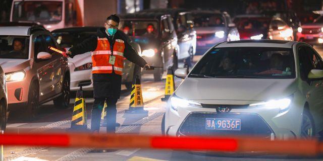 Man med mask dirigerar trafik i Wuhan i södra Kina TT NYHETSBYRÅN