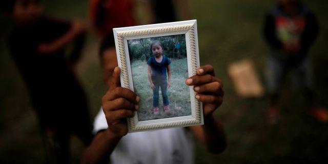 Jakelins bror Abdel Caal håller upp ett fotografi av systern. CARLOS BARRIA / TT NYHETSBYRÅN