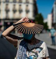 En kvinna med munskydd deltar i en tyst minut för pandemins offer i centrala Madrid. Manu Fernandez / TT NYHETSBYRÅN