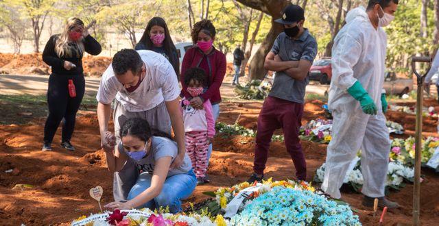 Släktingar sörjer vid graven till 65-åriga Maria Joana Nascimento, som misstänks ha dött av covid-19 i Sao Paulo i Brasilien.  Andre Penner / TT NYHETSBYRÅN