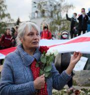 Kvinna i Minsk håller i Belarus gamla flagga.  TT NYHETSBYRÅN