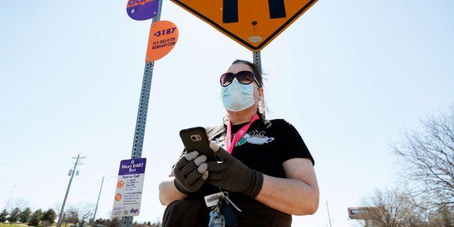 En kvinna i Iowa väntar på bussen iklädd handskar och ansiktsmak. Charlie Neibergall / TT NYHETSBYRÅN