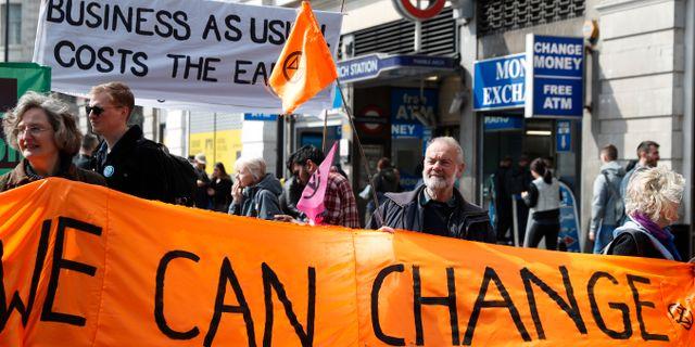 """Demonstranter håller upp en banderoll med texten """"Vi kan förändra"""" i centrala London.  Alastair Grant / TT NYHETSBYRÅN"""