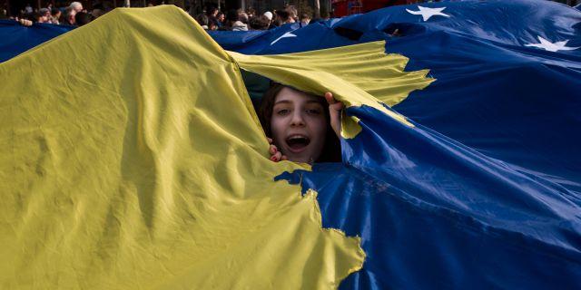 En flicka tittar fram bakom Kosovos flagga.  Visar Kryeziu / TT NYHETSBYRÅN/ NTB Scanpix