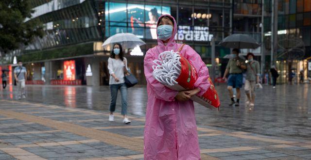 Kvinna säljer paraplyn i virusdrabbat Kina. Ng Han Guan / TT NYHETSBYRÅN