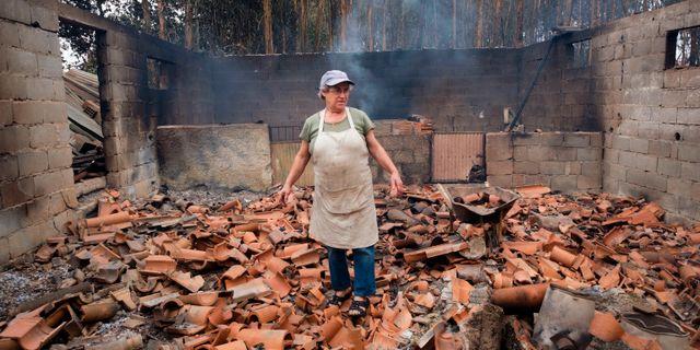 Inocencia Rodrigues, 64, går igenom sitt nedbrunna skjul i byn Sao Joaninho i norra Portugal.  Sergio Azenha / TT NYHETSBYRÅN