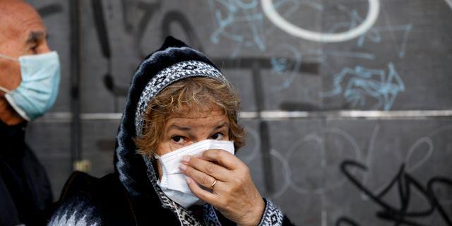 En kvinna köar utanför en bank i Buenos Aires, efter att bankerna öppnat för att låt människor hämta sina pensionsbetalningar.  Natacha Pisarenko / TT NYHETSBYRÅN