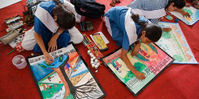 Indiska skolbarn gör teckningar om miljön. Rajesh Kumar Singh / TT NYHETSBYRÅN