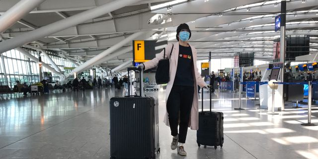 En kvinna med ansiktsmask på Heathrows flygplats i London.  Kirsty Wigglesworth / TT NYHETSBYRÅN