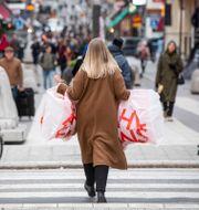 En kvinna bär på plastpåsar på Drottninggatan i Stockholm.  Fredrik Sandberg/TT / TT NYHETSBYRÅN