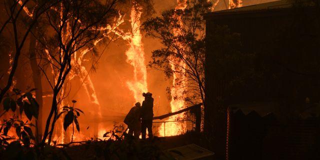 Branmän skyddar ett hem i Sydneyområdet från lågorna. STRINGER / TT NYHETSBYRÅN