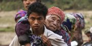 Civila flyr över en flod i norra Burma.  ZAU RING HPARA / AFP