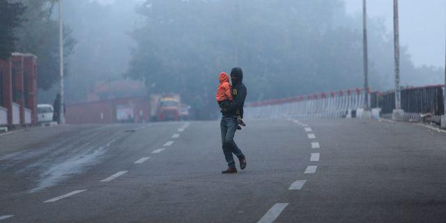 Man och barn i en indisk stad.  Channi Anand / TT NYHETSBYRÅN
