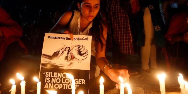 """En flicka med en skylt med texten """"Tystnad är inte längre ett alternativ"""" tänder ett ljus efter två uppmärksammade våldtäkter 2018.  Ajit Solanki / TT NYHETSBYRÅN/ NTB Scanpix"""