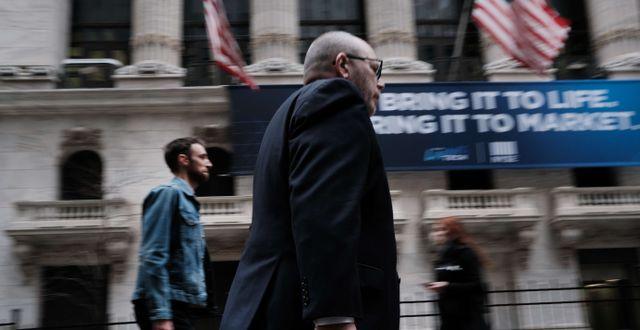 Illustrationsbild. Människor promenerar förbi New York-börsen.  SPENCER PLATT / TT NYHETSBYRÅN