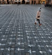 Små vita kors har målats på marken på Gamla stadens torg i Prag, för att minnas coronavirusets offer.  Petr David Josek / TT NYHETSBYRÅN
