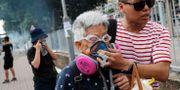 Äldre kvinna hjälps undan efter att polisen avfyrat tårgas TYRONE SIU / TT NYHETSBYRÅN