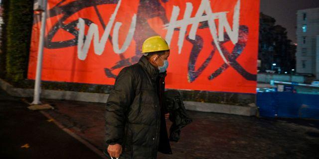 Kvinna med ansiktsmask i Wuhan i Kina, där smittan startade. HECTOR RETAMAL / AFP