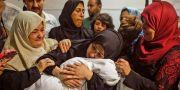Mamman till den åtta månader gamla flickan Leila al-Ghandour håller sitt barn hårt i famnen på ett bårhus, 15 maj.  MAHMUD HAMS / AFP