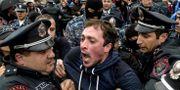 En demonstrant hålls tillbaka av poliser.  KAREN MINASYAN / AFP