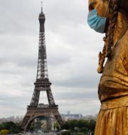 Staty med mask i Paris, Eiffeltornet syns på håll. Christophe Ena / TT NYHETSBYRÅN