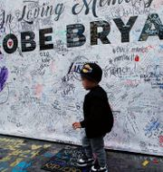 En pojke framför en minnesplats för den avlidne basketstjärnan Kobe Bryant.  Damian Dovarganes / TT NYHETSBYRÅN